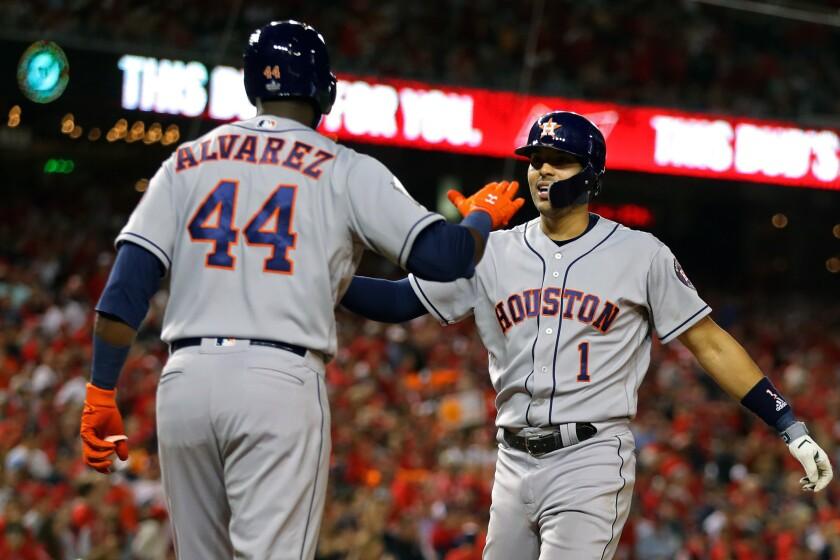 Houston Astros shortstop Carlos Correa, right, is congratulated by teammate Yordan Alvarez.