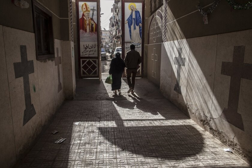 FILE - In this Tuesday, Jan. 6, 2015 file photo, Coptic Christians walk outside St. Markos Church in Minya, south of Cairo, Egypt. A Muslim mob ransacked and torched seven Christian homes in a province south of the Egyptian capital, Cairo, after rumors spread that a Christian man had an affair with