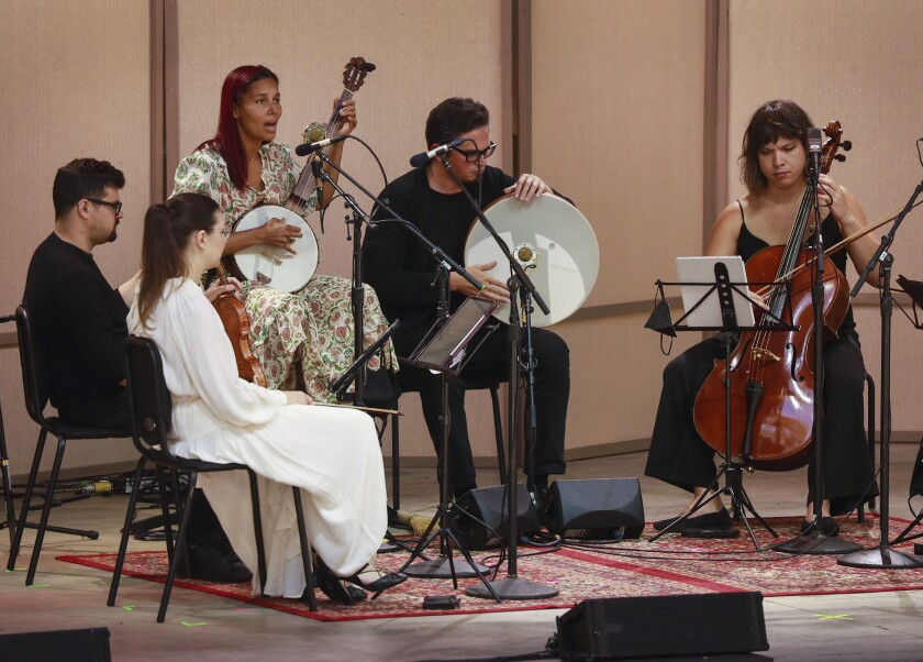 Five people play instruments, including a cello and a banjo