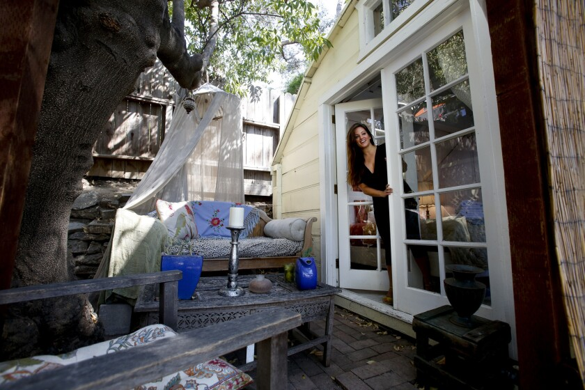 Hope Arnold peers out of her bedroom where she set up a sitting area next to the bedroom for guests to enjoy in the Silver Lake neighborhood of Los Angeles. She rents out her bedroom and sometimes her home through Airbnb to help her make ends meet and pay her bills.