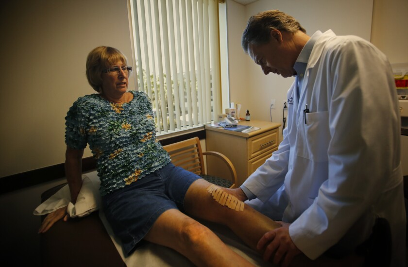 At Hoag Hospital in Irvine, orthopedic surgeon James Cailouette examines Carolyn Rondou a week after her knee replacement operation. Rondou's previous surgery on the right knee was bundled into one flat rate for surgery and related care, along with a warranty if something goes wrong.