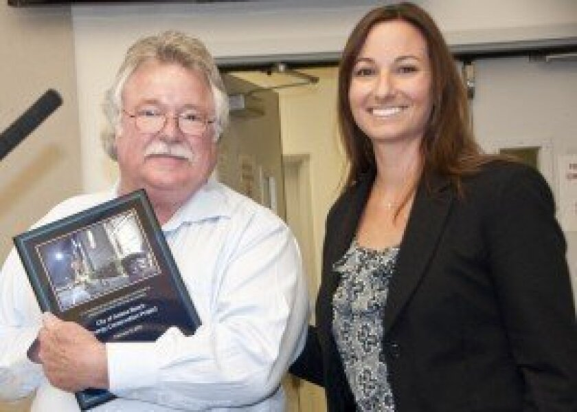 Deputy Mayor Tom Campbell accepts a plaque from Chevron Energy Solutions spokeswoman Trish Willhite on Feb. 13 to commemorate the completion of a $1.4 million energy-saving project. Photo/Claire Harlin