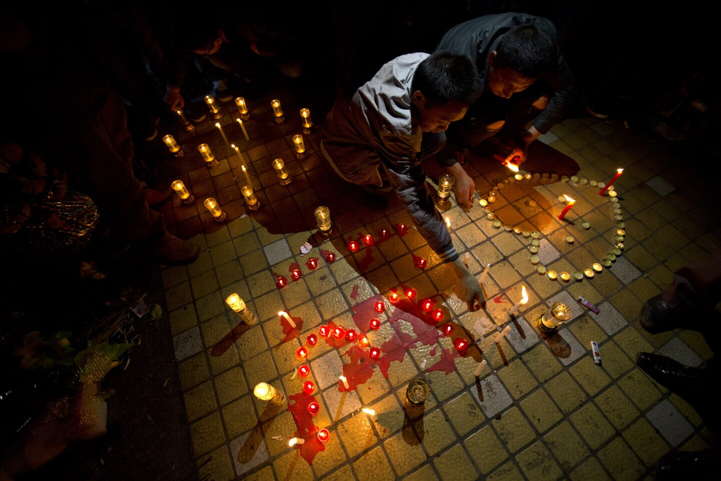 Two men light candles before a group prayer for the victims on a square outside the Kunming Railway Station where assailants slashed scores of people with knives the night before.