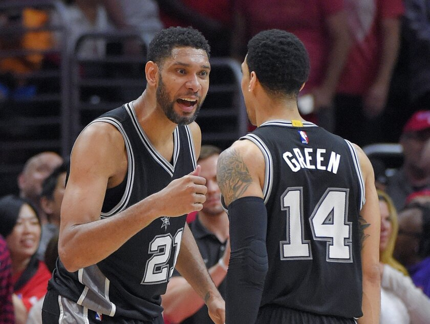 San Antonio Spurs forward Tim Duncan, left, celebrates with guard Danny Green during the final seconds of Game 5 of a first-round NBA basketball playoff series against the Los Angeles Clippers, Tuesday, April 28, 2015, in Los Angeles. The Spurs won 111-107. (AP Photo/Mark J. Terrill)