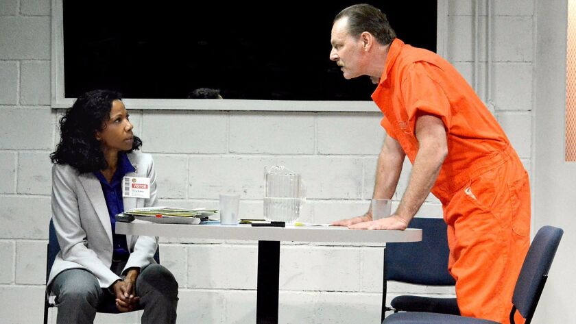 """Judith Moreland plays history professor Gloria and Bo Foxworth plays Rick, the supervisor of a private prison who has been arrested and placed in solitary confinement, in """"Building the Wall"""" at the Fountain Theatre. (Ed Krieger)"""