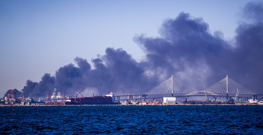 A large, drifting plume of black smoke rises behind a waterfront area