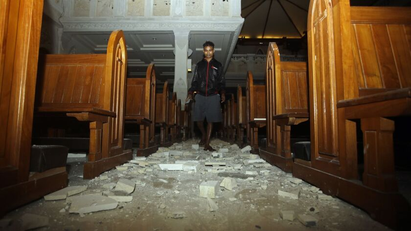A man walks inside a cathedral where debris has fallen after an earthquake in Bali, Indonesia, Sunday, Aug. 5, 2018.