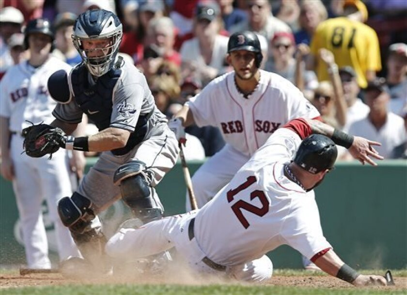 Boston Red Sox's Mike Napoli (12) slides safely into home as San Diego Padres catcher Nick Hundley gets the throw late during the fifth inning of a baseball game at Fenway Park in Boston on Thursday, July 4, 2013. (AP Photo/Winslow Townson)