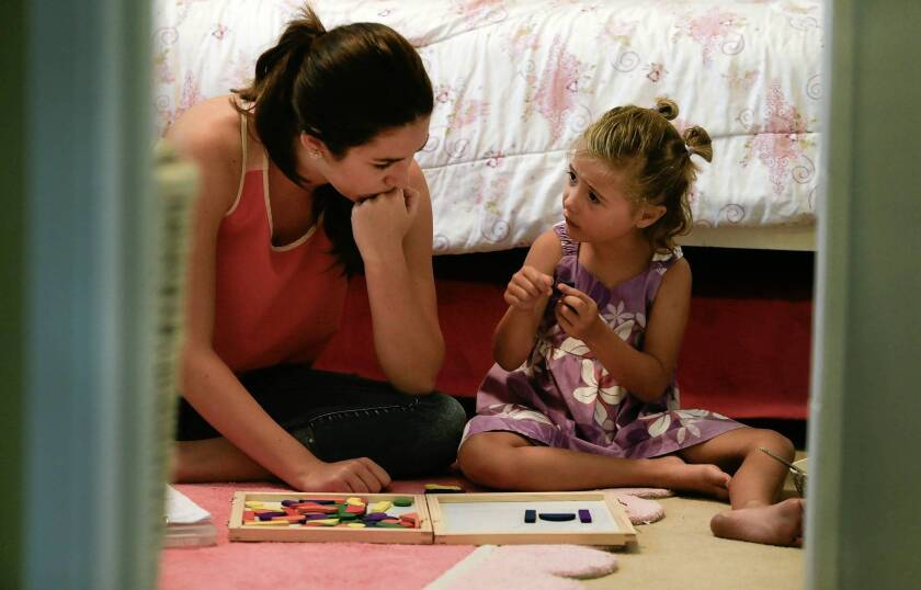 Six-year-old Naia Sullivan receives autism therapy in the bedroom of her home in San Diego from Hali Curry, a behavioral therapist. Naia's father said she had benefited greatly from applied behavior analysis, a treatment that will no longer be covered by the state.