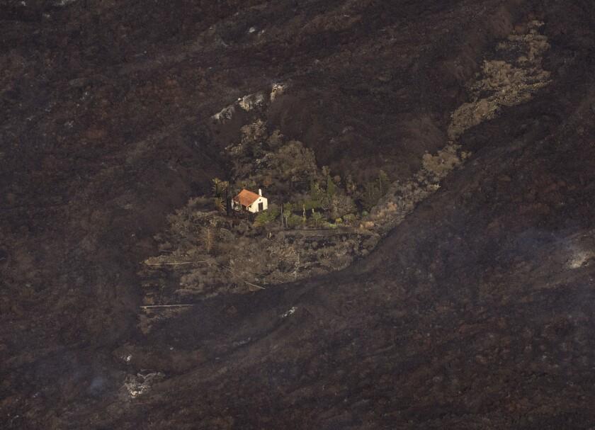 Lava procedente de una erupción volcánica rodean una casa en la isla de La Palma, en Islas Canarias, España, el 23 de septiembre de 2021. (AP Foto/Emilio Morenatti, Pool)