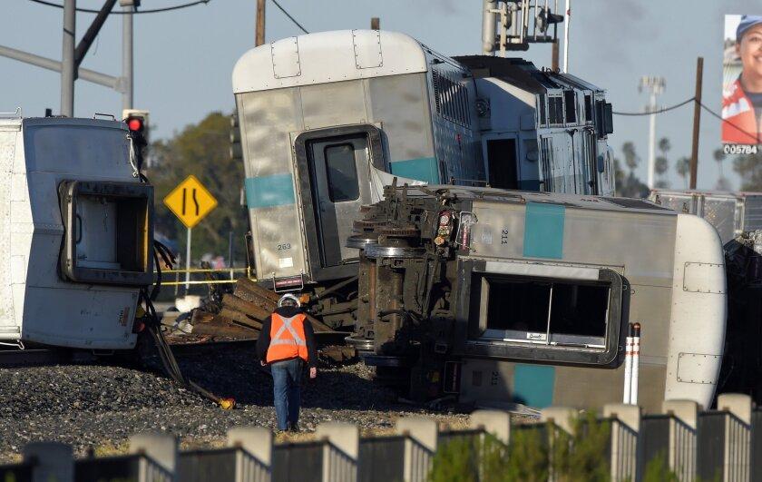 A worker walks along the tracks near the wreck of a Metrolink passenger train that derailed in Oxnard, Calif. on Feb. 24.