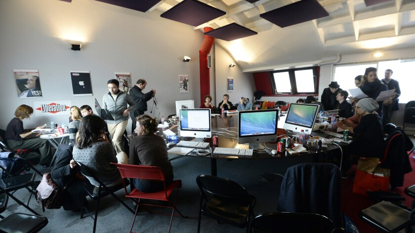 Charlie Hebdo staffers work at the Paris offices of the daily paper Liberation, where they have moved temporarily after the deadly attack at their building.
