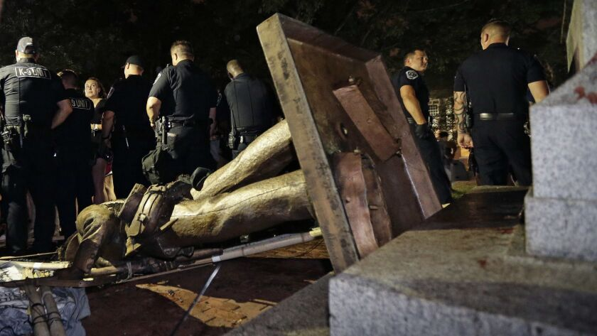 FILE - In this Aug. 20, 2018, file photo, police stand guard after the Confederate statue known as S