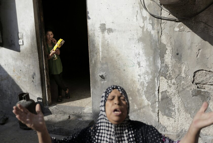 Palestinian Heygar Jendiyah, gestures as she speaks to the photographer, while her daughter Ranin, 10, stands background, at the house, partially destroyed by an Israeli strike earlier during the war, in the Sabra neighborhood of Gaza City, northern Gaza Strip, Thursday, July 31, 2014. The building