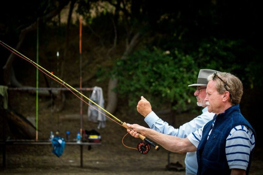 Chris Erskine, right, takes a fly-fishing lesson from Eric Callow at the Pasadena Casting Club.