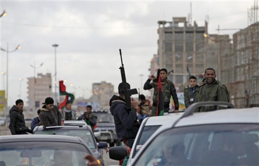 FILE - In this Sunday, Feb. 17, 2013 file photo, Libyan gunmen celebrate on the early morning of the second anniversary of the revolution that ousted Moammar Gadhafi, in Benghazi, Libya. More than 18 months since the end of Libya's civil war, the most attractive job for many of the young is still t
