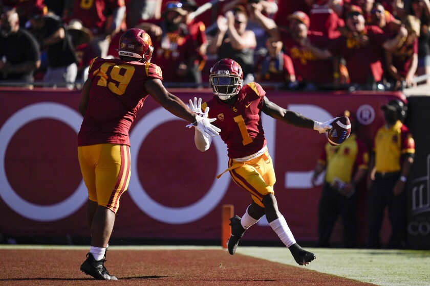 USC safety Greg Johnson, right, celebrates with defensive lineman Tuli Tuipulotu after returning an interception for a TD.