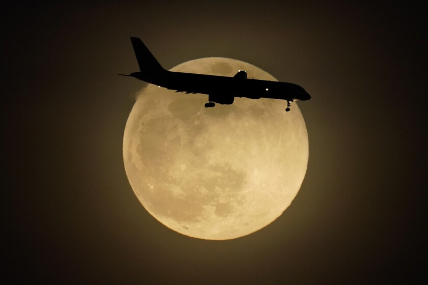 FILE - In this Monday, April 26, 2021 file photo, a jet is silhouetted by the rising moon as it approaches Louisville International Airport in Louisville, Ky. Air travel continues to recover from the pandemic, although it's still not close to normal. The Transportation Security Administration said that nearly 1.67 million people were screened at U.S. airport checkpoints on Sunday, May 2, 2021. (AP Photo/Charlie Riedel)