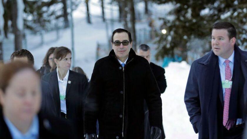 Treasury Secretary Steven T. Mnuchin walks through the snow at the World Economic Forum in Davos, Switzerland, on Wednesday.