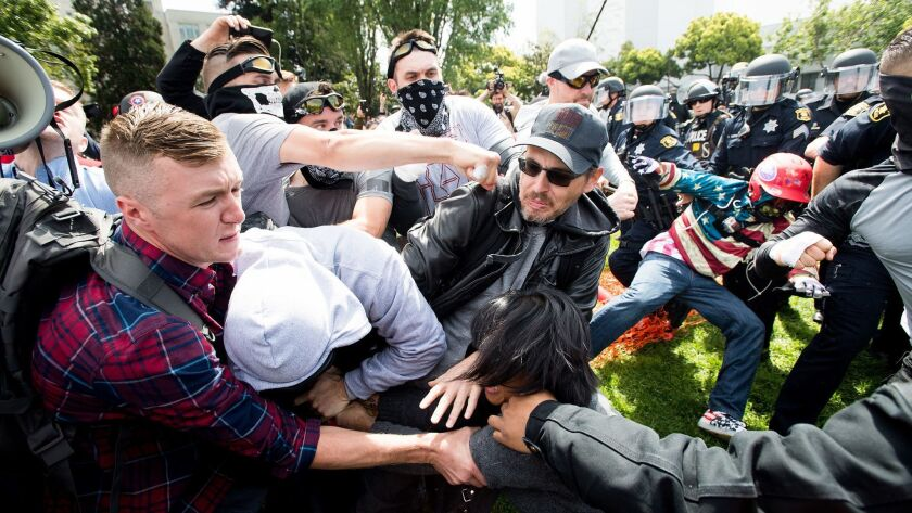 Robert Boman is shown punching a counter-protester in Berkeley while Aaron Eason, Michael Miselis and other RAM members stood beside him.