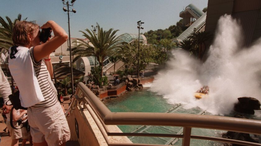 Visitors to Universal Studios Hollywood watch as riders of Jurassic Park -- The Ride splash down the final descent. A study found that the most expensive theme park to visit in the country is Universal Studios Hollywood.