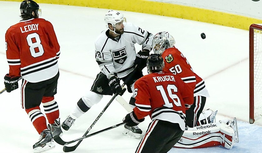 Kings center Jarret Stoll (28) watches the puck sail past Blackhawks goalie Corey Crawford for the winning goal in overtime in Game 7 on Sunday night in Chicago.