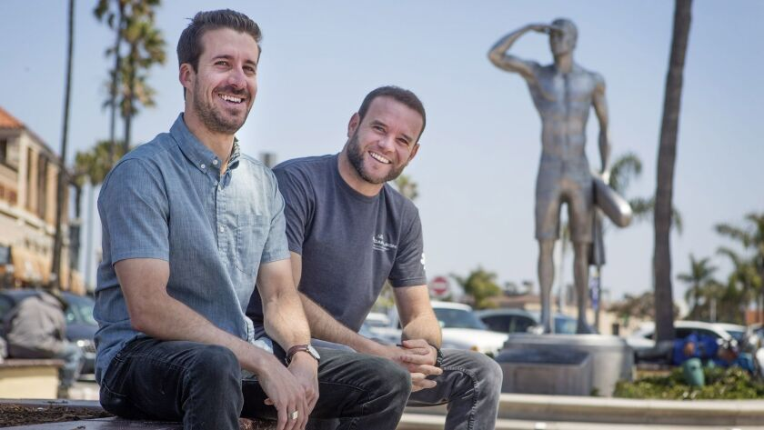 From left, Jack Murghardt and Tim Burnham pose for a photograph in front of the Ben Carlson statue a