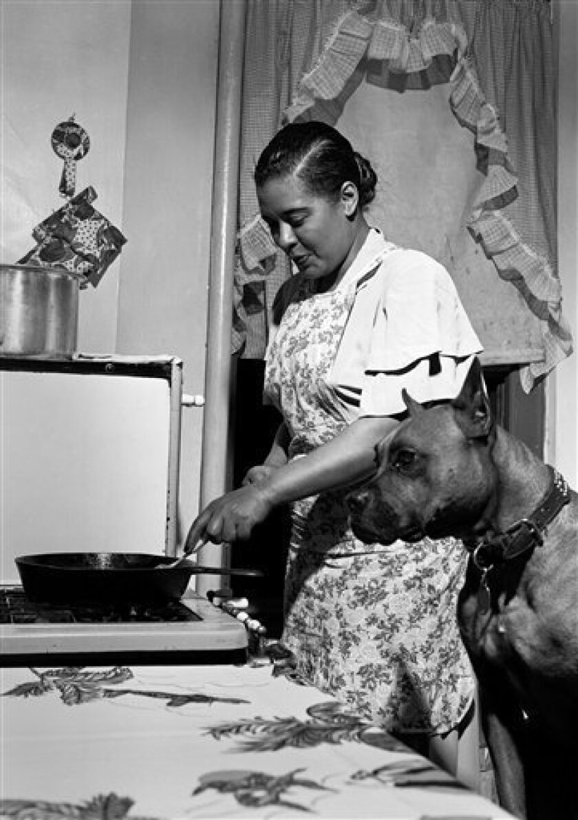 """This 1949 photo released by Herman Leonard Photography, shows Billie Holiday cooking a steak for her dog Mister in her apartment in the Harlem neighborhood of New York. The photographer, Herman Leonard, said she came to the door wearing a simple house dress and an apron and """"First I thought, this is the maid."""" But it was Holiday, one of the greatest voices of modern time, whom Leonard would continue to photograph throughout her life. (AP Photo/Herman Leonard Photography, LLC., CTSIMAGES)"""