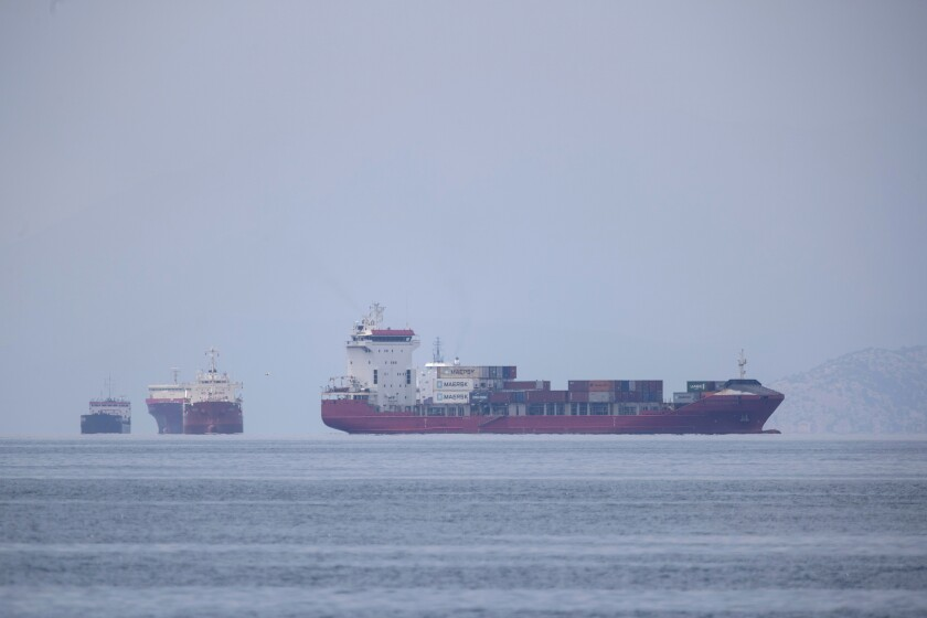 A cargo ship approaches the port of Piraeus as other ships are anchored, near Athens, Greece, Tuesday, May 26, 2020. During the new coronavirus pandemic, about 150,000 seafarers are stranded at sea in need of crew changes, according to the International Chamber of Shipping. Roughly another 150,000 are stuck on shore, waiting to get back to work. (AP Photo/Petros Giannakouris)