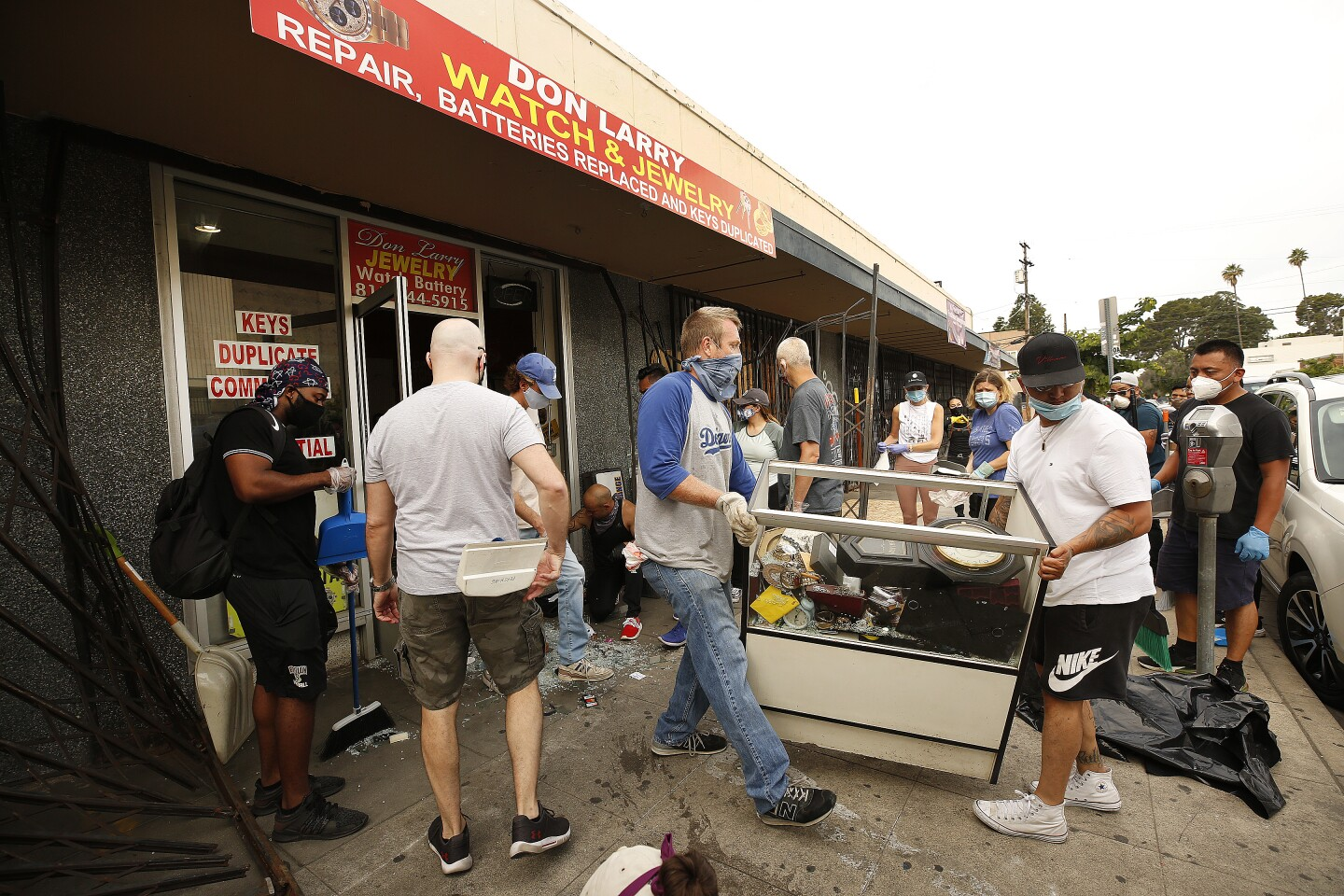 VAN NUYS, CA - JUNE 02: Volunteers work to sort through cases of jewelry inventory in the Don Larry Watch & Jewelry Repair store on Hamlin Street just off Van Nuys Blvd. People roamed the Van Nuys shopping district Tuesday morning to clean up and remove debris in the aftermath of the protest and looting of businesses along Van Nuys Blvd as numerous stores were attacked and at least one set on fire. Protestors again gathered in the midst of the coronavirus outbreak to protest the death of George Floyd, an unarmed black man who died last week in police custody after a white Minneapolis police officer pinned him down by his neck for several minutes. Van Nuys on Tuesday, June 2, 2020 in Van Nuys, CA. (Al Seib / Los Angeles Times)