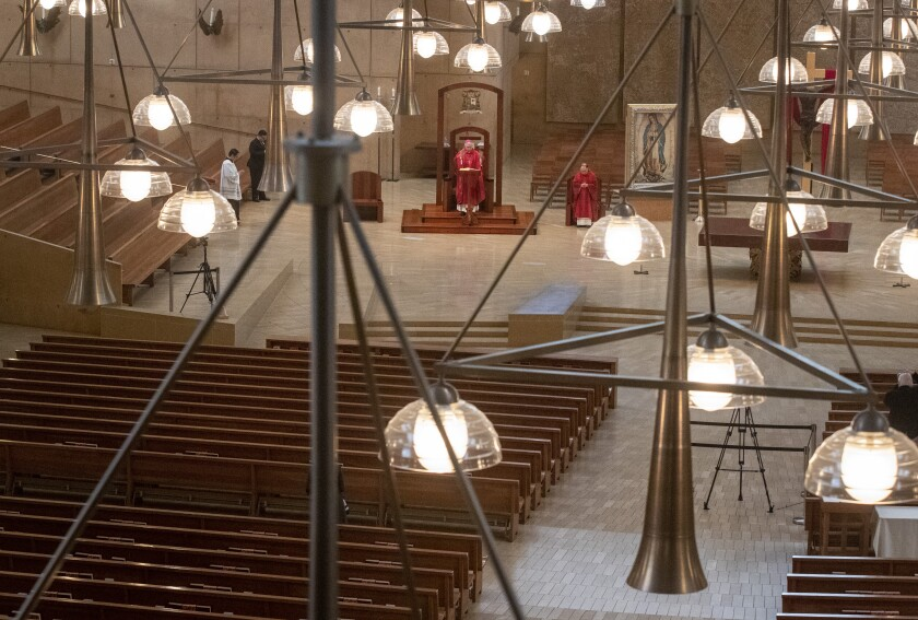 Clergy celebrate Good Friday in a nearly empty Cathedral of Our Lady of the Angels.