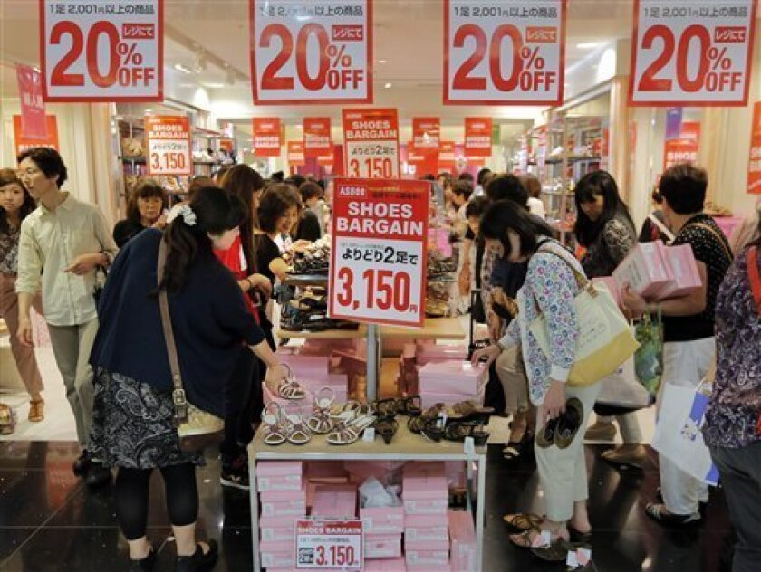 FILE - In this June 28, 2013 file photo, shoppers view shoes on sale at a department store in Tokyo Friday, June 28, 2013. Japan's economy grew at a slower-than-expected rate of 2.6 percent last quarter, suggesting demand has been slow to pick up despite strong public spending and ultra-lax monetary policies. The data released Monday, Aug. 12, 2013 by the Cabinet Office show the strongest contribution to growth coming from public spending and exports, while private investment weakened. (AP Photo
