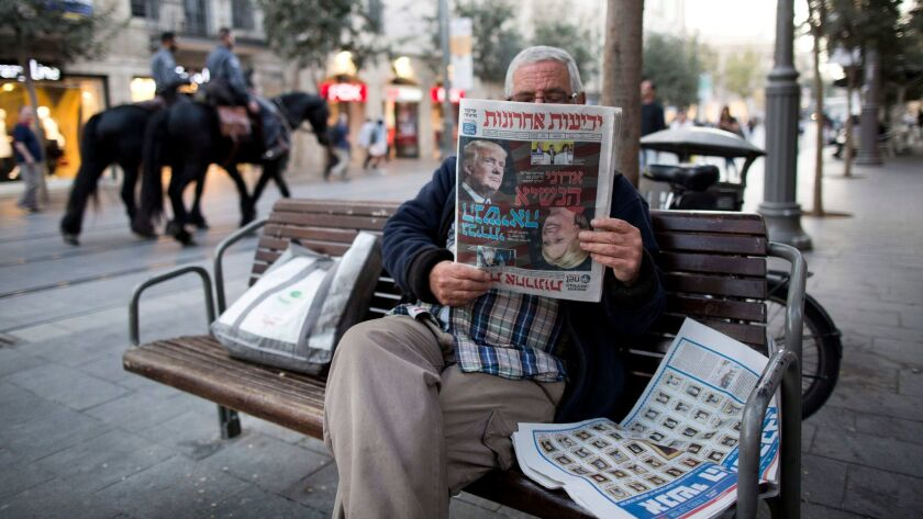 A man in central Jerusalem reads the Israeli newspaper Yediot Aharonot featuring coverage of the U.S. presidential election.
