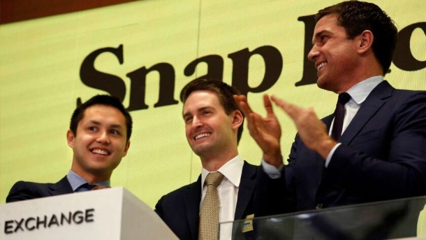 Snap Inc. CEO Evan Spiegel, center, rings the bell at the New York Stock Exchange last year as the company made its stock market debut.
