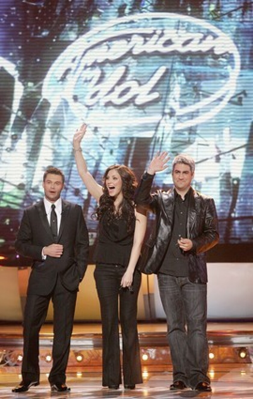 Host Ryan Seacrest, left, with season 5's pair of finalists, Katherine McPhee and eventual champion Taylor Hicks.