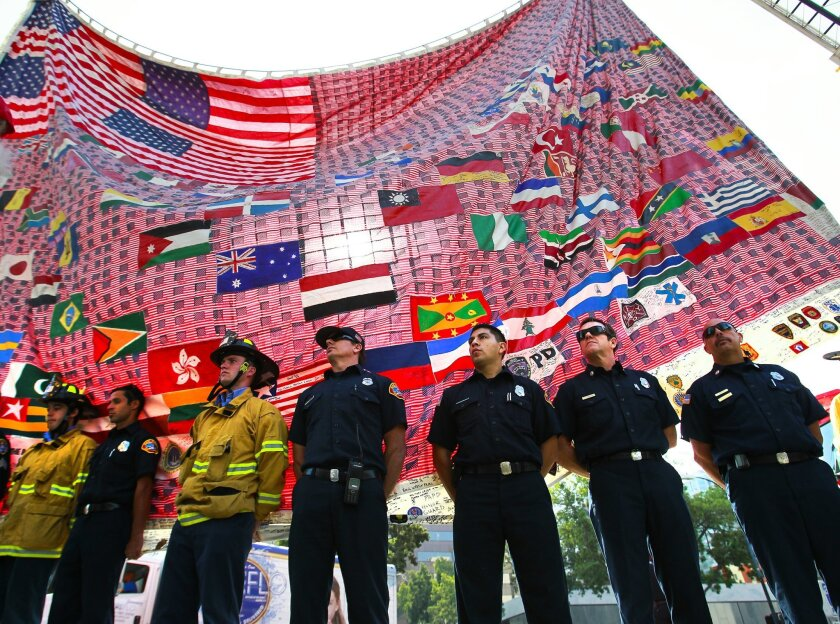 San Diego Fire-Rescue Department firefighters stand in front of the 9/11 Memorial Flag during  its last stop on its 13-year long worldwide tour at Civic Center Plaza.
