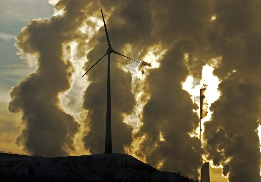 A wind turbine stands in front of a coal-fueled power plant in Gelsenkirchen, Germany, in December 2010.