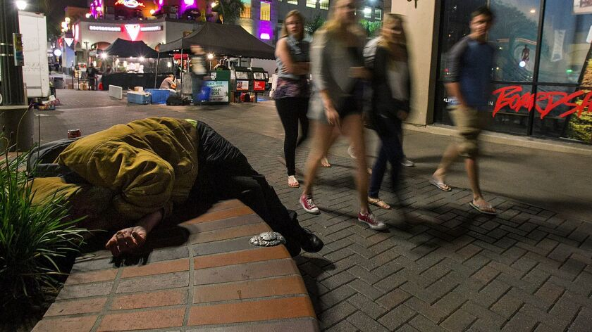 Crowds walk by a sleeping homeless man on Main Street in Huntington Beach in 2014.