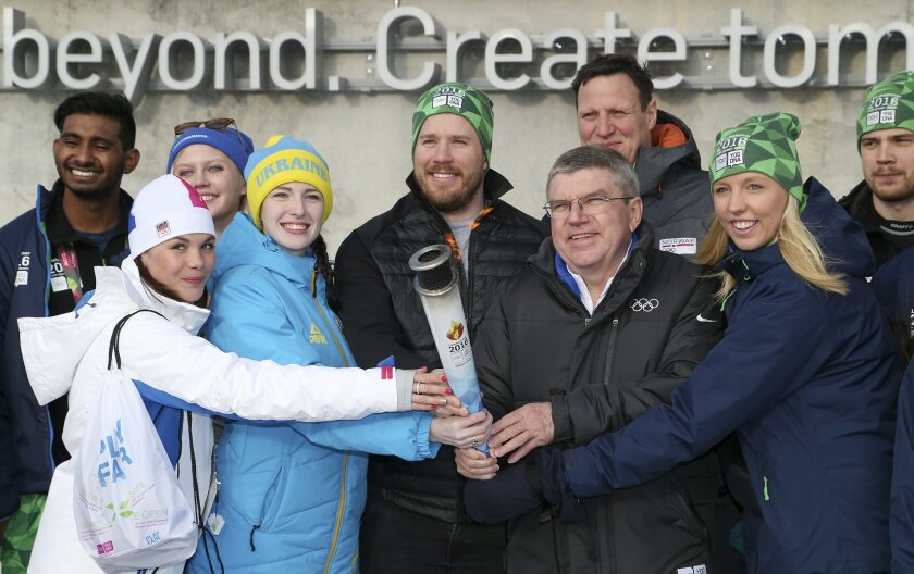 International Olympic Committee President Thomas Bach, 3rd right, front row, poses for the medida with the torch of the Lillehammer 2016 Winter Youth Olympic Games with Olympic Gold medalist Kjetil Jansrud of Norway, center, and young ambassadors and volunteers of the games, in Lillehammer, Norway,