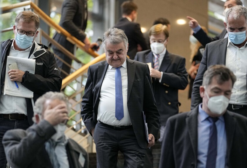 North Rhine-Westphalia's Interior Minister Herbert Reul, center, leaves after a press conference in Duesseldorf, Germany, after raids in severals German cities, Wednesday, Oct. 6, 2021. German police have carried out large-scale raids in 25 cities in connection with a suspected money-laundering network alleged to have funneled more than $162 million in ill-gotten gains abroad. (AP Photo/Martin Meissner)