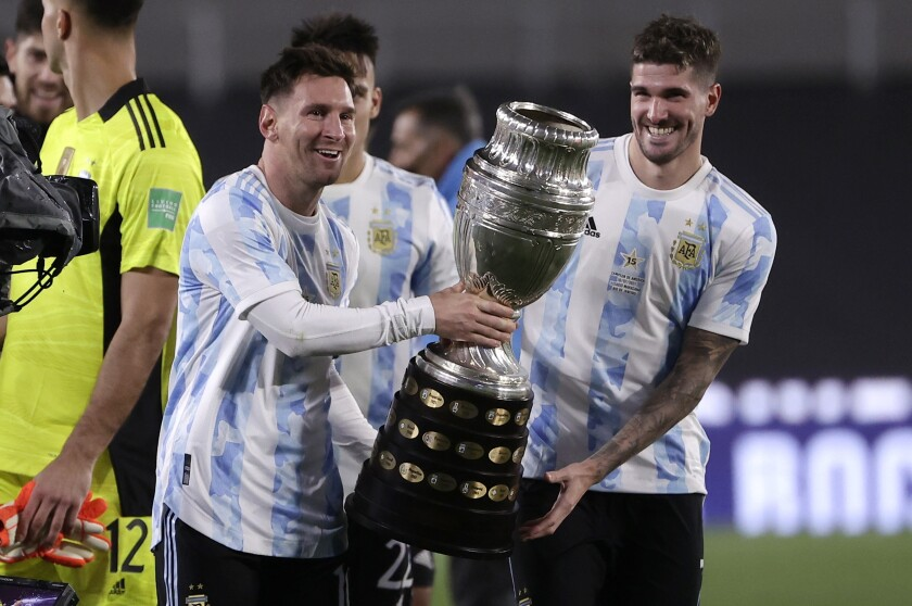 Argentina's Lionel Messi, left, and his teammate Rodrigo De Paul hold the Copa America trophy at the end a qualifying soccer match for the FIFA World Cup Qatar 2022, against Bolivia in Buenos Aires, Argentina, Thursday, Sept. 9, 2021. (Juan Roncoroni/Pool via AP)