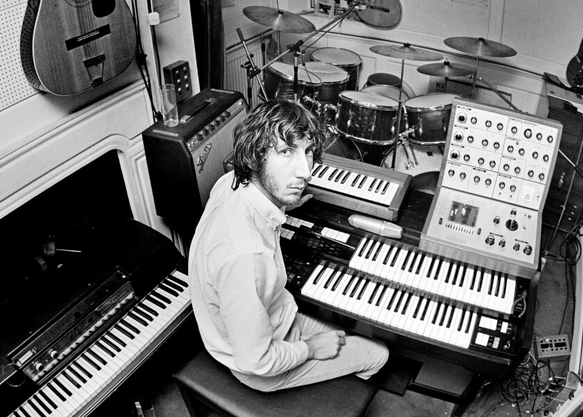 Guitarist Pete Townshend of the Who, in the recording studio at his home in Twickenham, London, 1970. On the wall, left, are a Coral Hornet electric guitar and a Harmony Sovereign 12-string acoustic. On the right is an EMS VCS3 mk1 synthesizer resting on a Lowrey Berkshire Deluxe TBO-1 organ.
