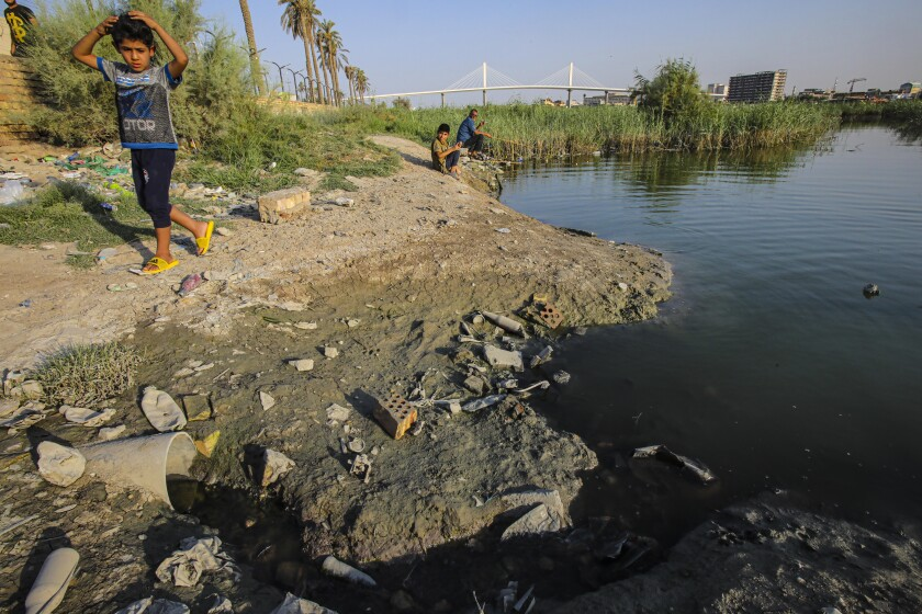 A child walks on the bank of the Shatt al-Arab waterway in Basra, Iraq on July 13, 2020. Iraq's minister of water resources said Thursday, July 16, 2020 that severe shortages loom ahead if Iraq and neighboring Turkey fail to strike agreements over irrigation and dam projects. (AP Photo/Nabil al-Jurani)