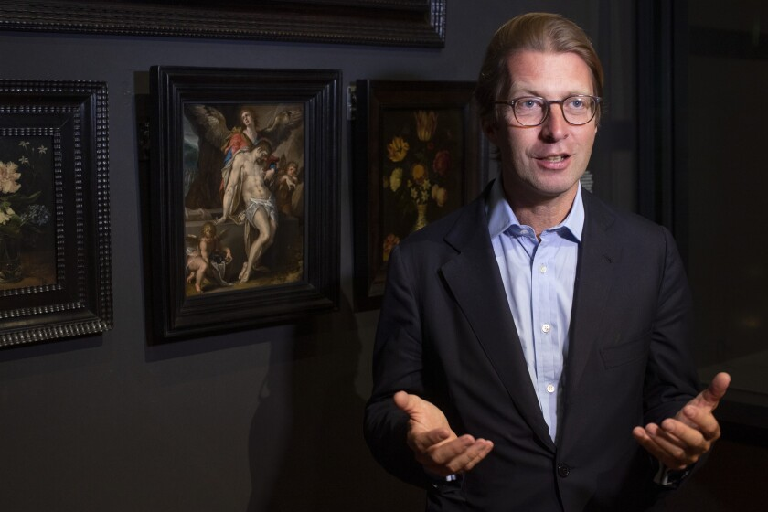"Rijksmuseum director Taco Dibbits, standing in front of Bartholomeus Spanger's ""Body of Christ Supported by Angels"" oil on copper painting, left, discusses the gift of the major painting the cultural institution received to underscore support for the victims of the coronavirus pandemic and the crisis that museums face world wide, which went on display in Amsterdam, Netherlands, Monday, June 1, 2020. The Dutch government took a major step to relax the coronavirus lockdown, with bars, restaurants, cinemas and museums reopening under strict conditions. (AP Photo/Peter Dejong)"