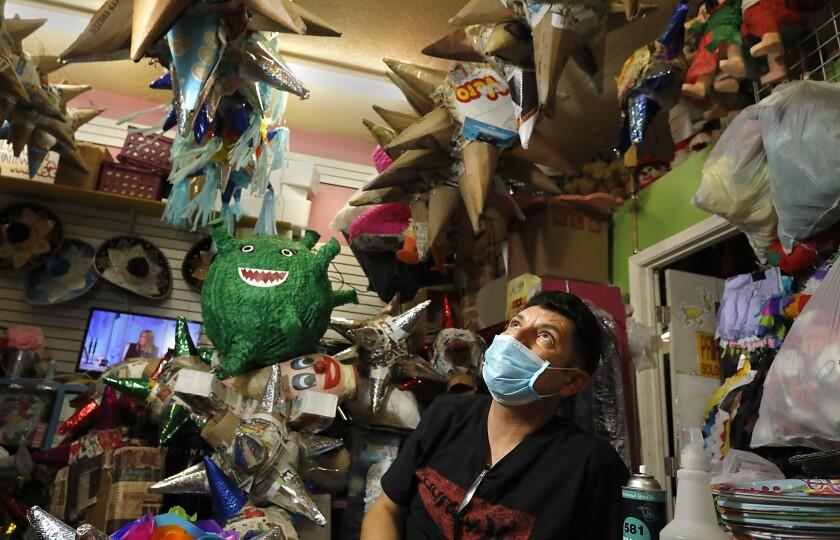 Robert Diaz, owner of La Casa de Las Pinatas in City Heights, looks at pinatas hanging from ceiling.