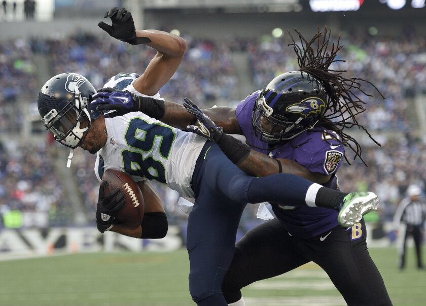 FILE - In this Dec. 13, 2015, file photo, Seattle Seahawks wide receiver Doug Baldwin (89) is hit by Baltimore Ravens free safety Kendrick Lewis as Baldwin scores a touchdown during an NFL football game in Baltimore. The Seahawks face the Carolina Panthers in a playoff game Sunday; a key matchup wi