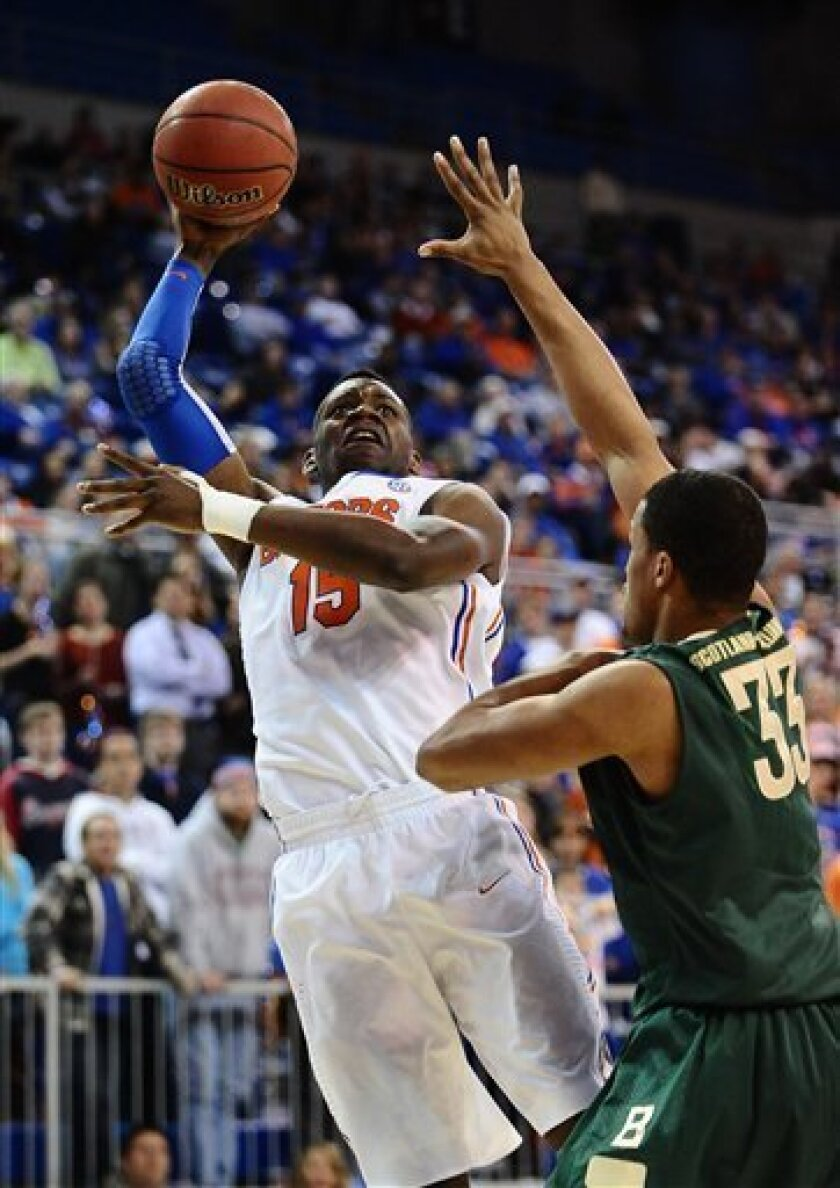 Florida's Will Yeguete (15) shoots for two points as UAB's Alexander Scotland-Williamson (33) tries to stop the shot during the first half of an NCAA college basketball game in Gainesville, Fla., Tuesday, Jan. 3, 2012. (AP Photo/Phil Sandlin)
