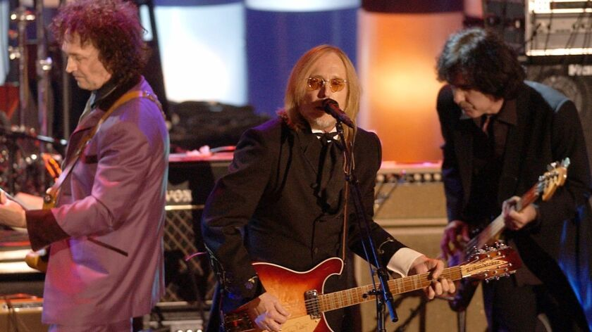 Tom Petty, center, and the Heartbreakers, perform after being inducted into the Rock and Roll Hall of Fame on March 18, 2002