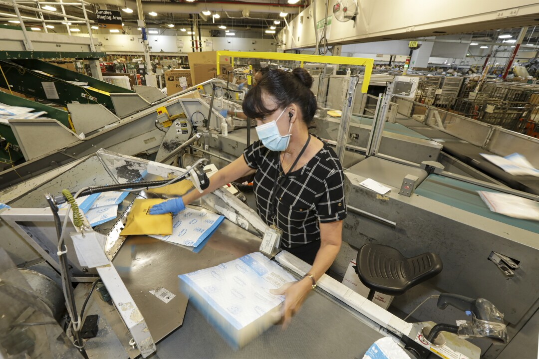 A woman wearing a mask and one glove processes packages.