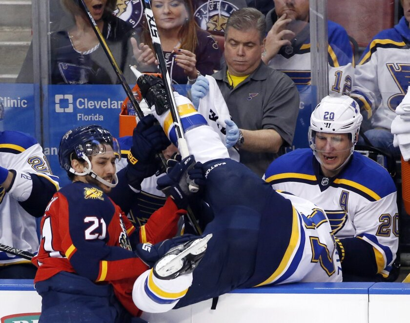 Florida Panthers center Vincent Trocheck (21) shoves St. Louis Blues left wing Jaden Schwartz (17) over the boards during the third period of an NHL hockey game, Friday, Feb. 12, 2016, in Sunrise, Fla. The Blues defeated the Panthers 5-3. (AP Photo/Wilfredo Lee)